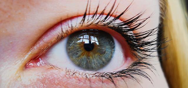 Gros plan sur les yeux bleu et vert d'une femme.