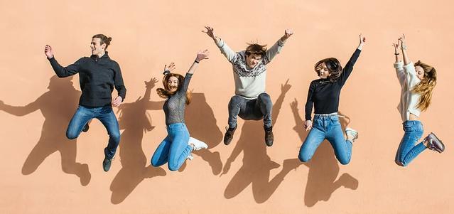 Un groupe d'amis qui saute dans les airs tout en souriant et rigolant