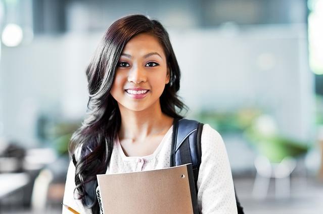 Une souriante adolescente portant un sac à dos et ses cahiers.