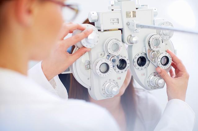 Une jeune femme derrière un phoroptère pendant que l'ophtalmologue lui vérifie ses yeux durant un examen oculaire.