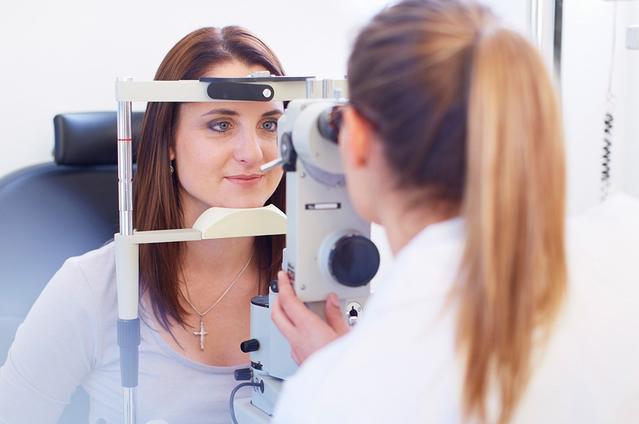 Plan d'une jeune femme regardant à travers une caméra rétinienne pendant que l'ophtalmologue regarde de l'autre côté.