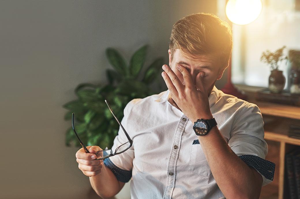 Image d'un homme enlevant ses lunettes pour se frotter les yeux.