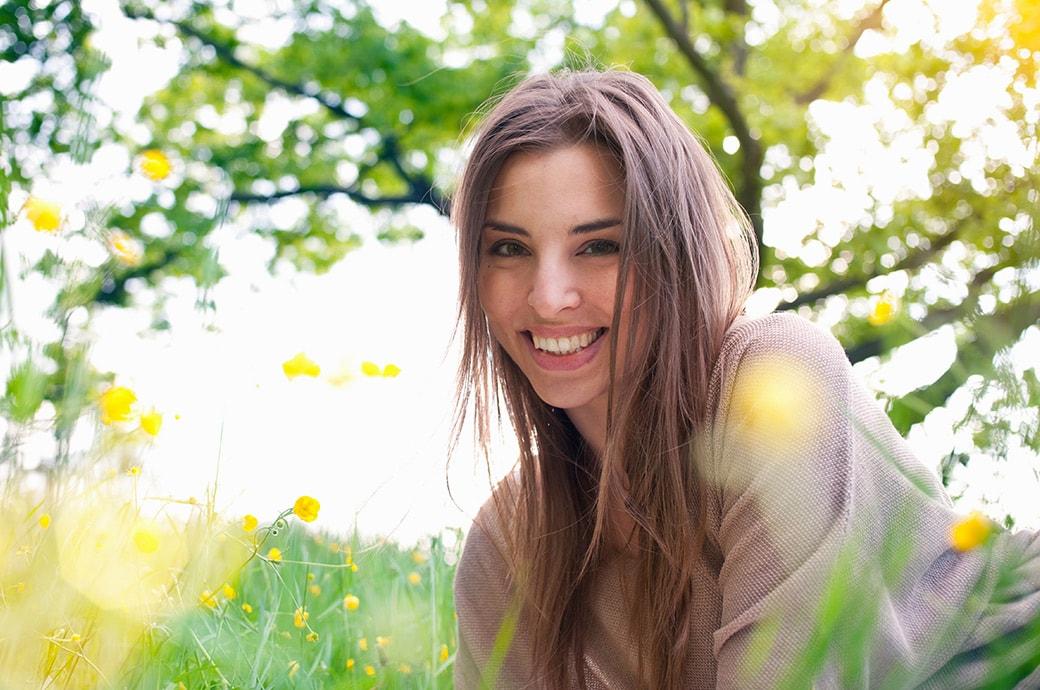 Une femme adulte, souriante étendue dans l'herbe profitant du soleil.