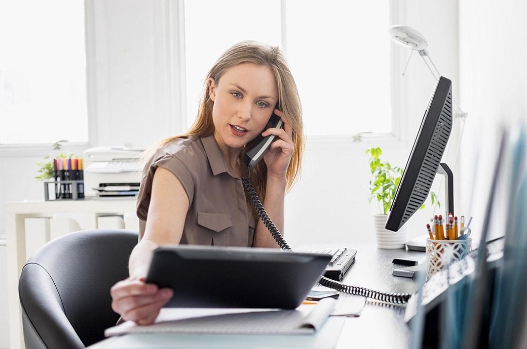 Une femme travaillant à son bureau, regardant une tablette tout en passant un appel téléphonique