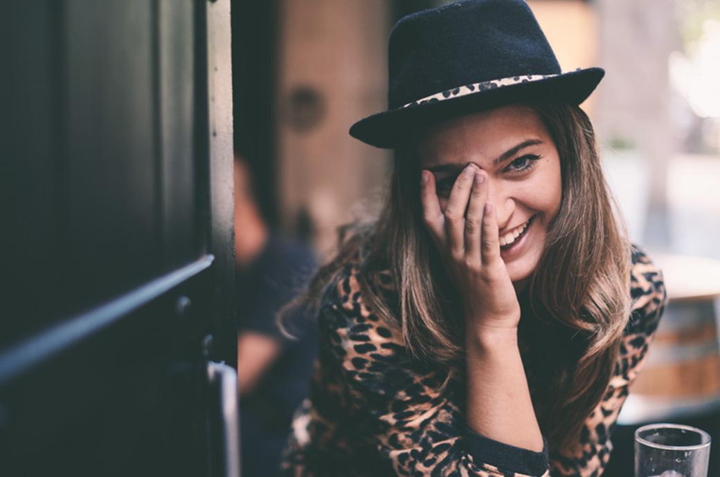 Image d'une femme en extérieur cachant son oeil.