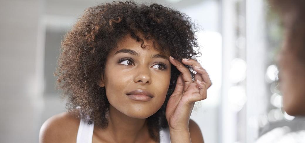 Une jeune femme regardant ses yeux dans le miroir.